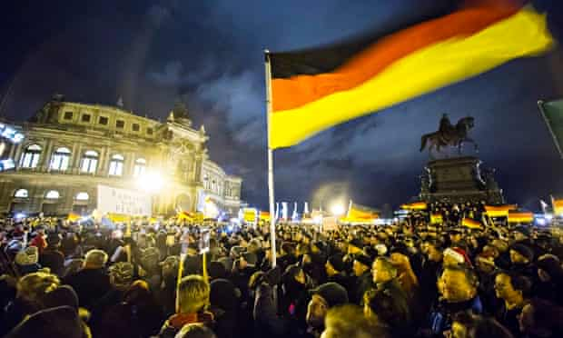 Participants hold German national flags during a demonstration by anti-immigration group Pegida outs