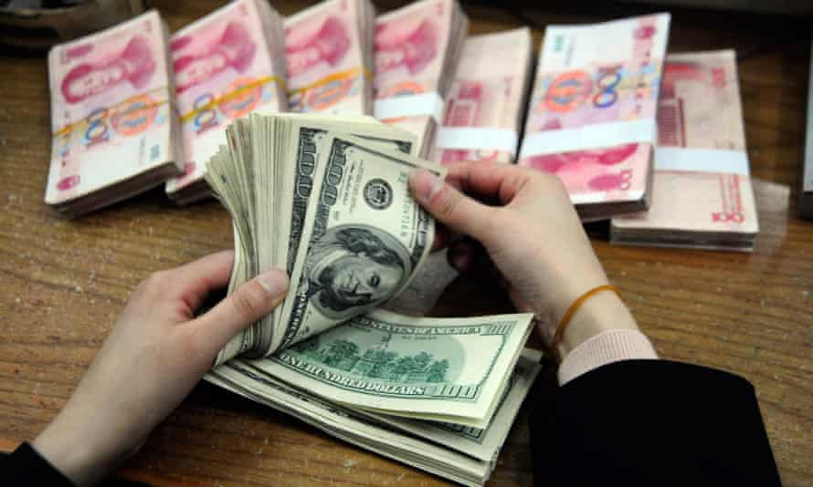 A Chinese bank worker counts a stack of US dollars together with stacks of 100 Chinese yuan notes at a bank in Hefei, east China's Anhui province on March 9, 2010.  China and the USA have pledged action to reduce the costs of climate change.