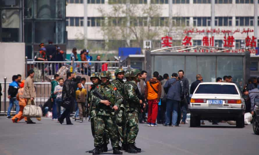 Paramilitary policemen stand guard near the exit of the South Railway Station, in Urumqi, Xinjiang. Authorities there say everyone buying a computer or mobile phone must now register personal details.