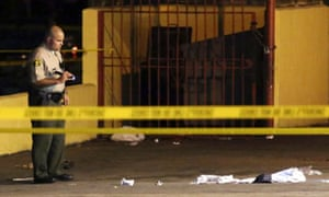 A Los Angeles sheriff's deputy inspects the scene where a man was killed in a hit-and-run involving the rap music mogul Marion 'Suge' Knight.