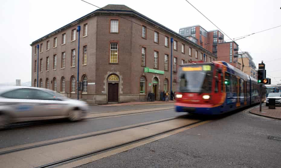 The 'Supertram' rumbles past West Street job centre in Sheffield.