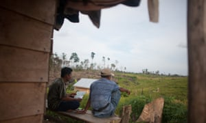 Two migrant farmers originally from Java sat by a house inside the Harapan Rainforest in Sumatra, Indonesia. Harapan is managed by a consortium of bird conservation groups, led by the RSPB. The project aims to restore an area of degraded forest close to the size of London.
