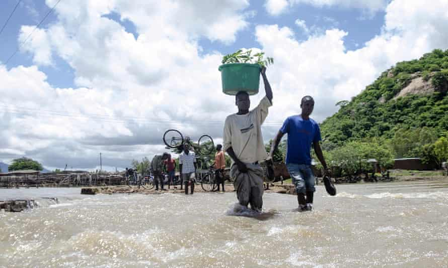 People cross a river with their belongings where a bridge once stood in Phaloni, Southern Malawi,  January 22, 2015. Malawi has been affected by flooding caused by heavy rains, with scores of people having died and some 200,000 displaced.