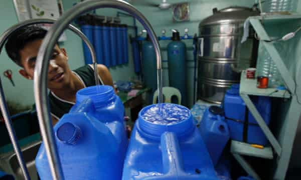 A Filipino fills canisters with drinking water for sale in a poor district of Quezon City, east of Manila, Philippines 21 March 2013.