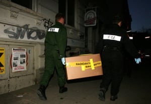 Two policeman carry a cardboard box, secured with tape marked radioactive from an apartment building in Hamburg-Ottensen