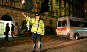A British police officer blocks traffic as a police van takes up a position outside the Millennium hotel in Grosvenor Square in London