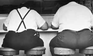 Two obese men sitting on four stools Men in a Diner