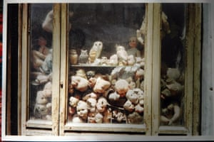 broken pieces of dolls in a glass cabinet