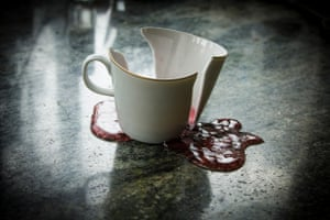 a broken tea cup with red liquid pouring out