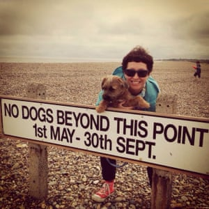 a woman holding a dog behind a no dogs beyond this point sign