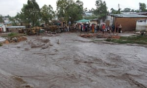 Villagers in Malawi stand beside a flooded street.