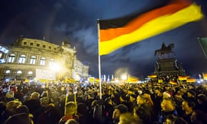 German flags fly at a Dresden Pegida march.