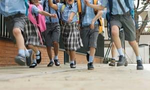 Schoolchildren running down a street