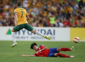 South Korea's Kim Jin-Su slides in to tackle Mathew Leckie.