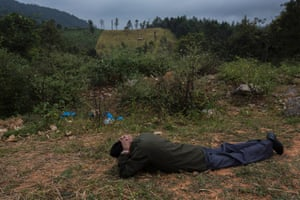 Kampuang Dalaseng lies on the ground demonstrating how he would hide from the bombs during the secret war.