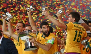 Mile Jedinak seems shocked to be holding the Asian Cup after his side's dramatic victory.