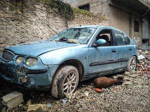 An unexploded bomb by an abandoned car