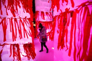 A woman looks for space to hang her red ribbon bearing her wish on an ice sculpture