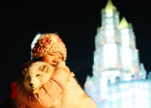 A visitor takes a souvenir picture with a white fox