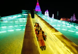 Children slide down an ice sculpture