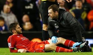 Adam Lallana receives treatment after sustaining an injury against Leicester.