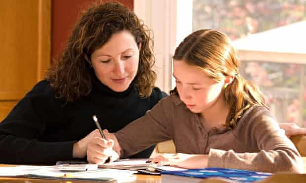 Mother helping daughter with her home schooling homework in kitchen.