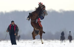 A man struggles to control his horse before a traditional Epiphany celebration race in Pietrosani, Romania