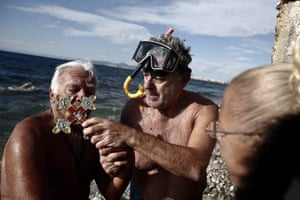 Nikos Konstantopoulos holds a cross as a swimmer kisses it in Paleo Faliro, near Athens