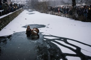 A drummer wades in the icy waters of the Tundzha river in Kalofer, Bulgaria