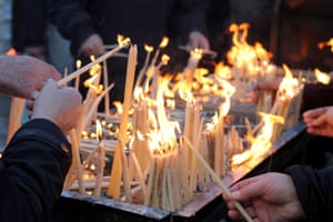 People light candles after an Epiphany mass in Durres, Albania