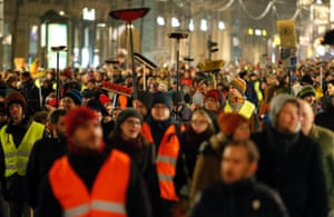 Participants carry brooms as they protest against a demonstration called by anti-immigration group Pegida, in Dresden