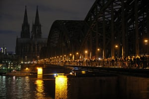 Cologne Cathedral's lighting is switched off to make a statement against racism as people cross the Hohenzollernbrucke bridge during protests against Pegida in Cologne