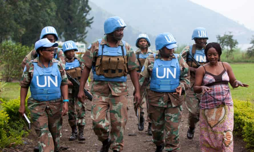 """Major Steven Matodon, public information officer for the South African U.N. brigade, center, leads a handpicked group of mostly female U.N. soldiers on a """"mission"""" to scope out a park to hold an upcoming Women's Day celebration, near Sake, D.R. Congo, July 26, 2014.   They are treating us as women whereas we are soldiers,  says Lieutenant Colonel Zukiswa Caga, the brigade's gender advisor, third from right."""