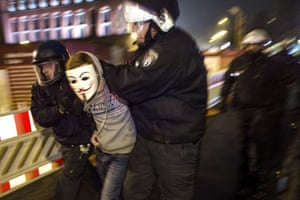 An anti-Pegida-protester wearing a Guy-Fawkes-mask is arrested by the police for refusing to leave the street during a demonstration in Berlin
