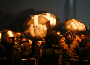 Demonstrators hold umbrellas as they protest in Berlin