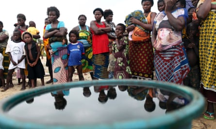 Villagers stand near a container containing crude oil collected by villagers as sample at the shore of the Atlantic ocean near Orobiri village, days after Royal Dutch Shell's Bonga off-shore oil spill, in Nigeria's delta state December 31, 2011.