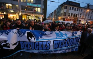 """People hold a banner reading """"Refugees welcome"""" as they take part in a protest against a rally by Pegida in Rostock"""