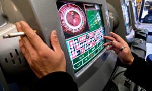 Hands of a gambler placing a bet on a machine