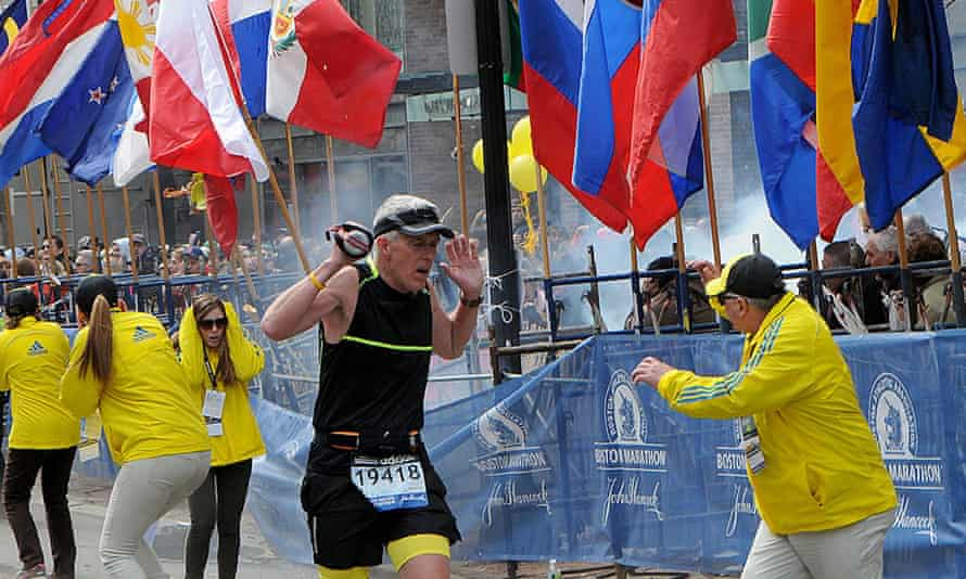 A runner and race officials react to an explosion during the 2013 Boston Marathon.