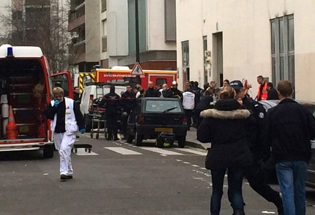 Firefighters and police in front of the Charlie Hebdo offices