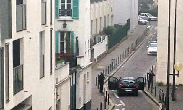 Armed men face police officers near the offices of Charlie Hebdo
