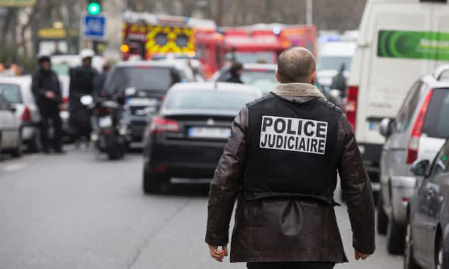 A policeman walks near the site of an armed attack at the headquarters of French satirical magazine 'Charlie Hebdo', in Paris, France, 07 January 2015. According to news reports, several people have been killed in a shooting attack at satirical French magazine Charlie Hebdo in Paris.  EPA/ETIENNE LAURENT
