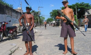Armed bandidos, with pixelled faces, stand guard in Vila Aliança.
