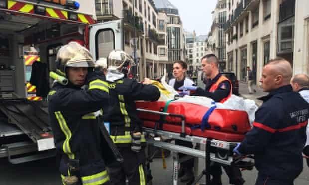 Firefighters carry an injured man outside of the offices of the Charlie Hebdo offices in Paris