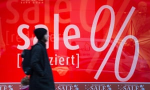 A shopper strolls past a sign offering reduced prices at a December sale in Dusseldorf, Germany. Economists fear an overall trend to lower prices and deflation.