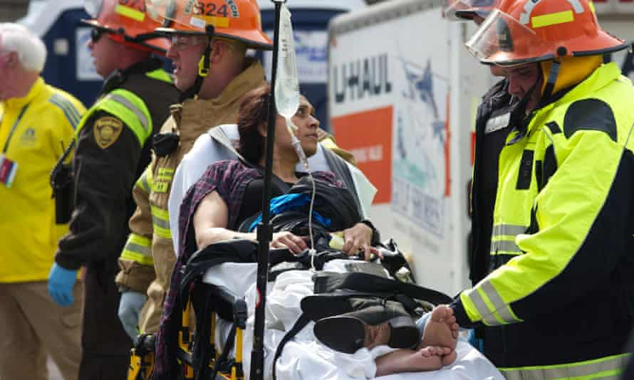 Emergency responders aid a woman injured in one of the bomb blasts.