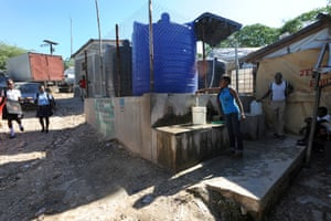 Camp Acira residents fill their containers with clean water from this blue tank.
