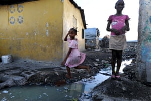 Girls at Cité Soleil play close to dirty standing water which is blighting the lives of residents.