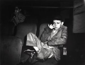 Boy with finger in his mouth in a movie theatre, New York