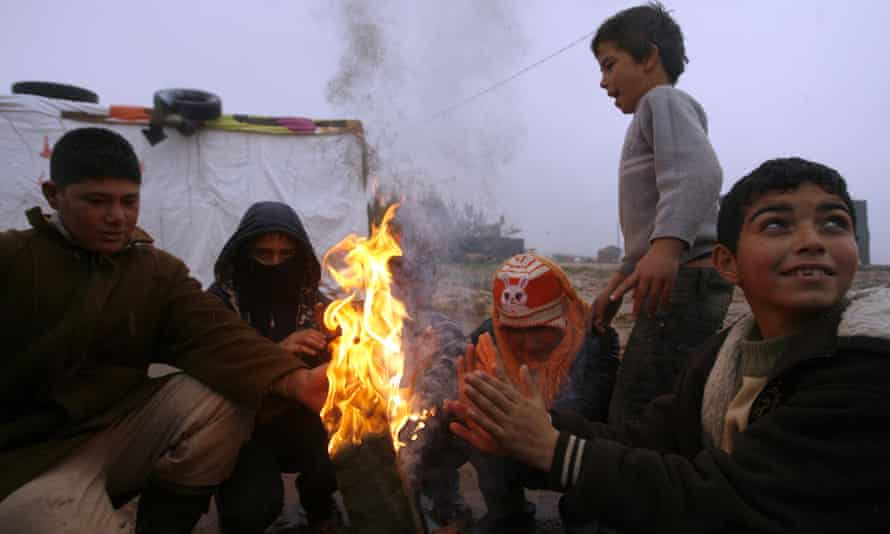 Syrian refugee children warm themselves over a fire at a refugee camp in Lebanon.